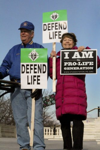 St.  John Bosco Catholic Church parishioners David Fairbank, left, and Mary Simonds hold up their signs at the 2015 March for Life. Photo courtesy of Lee Dieter